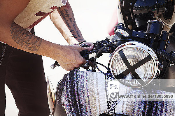 Mittelsektion eines Mannes  der ein Motorrad an einer Tankstelle repariert