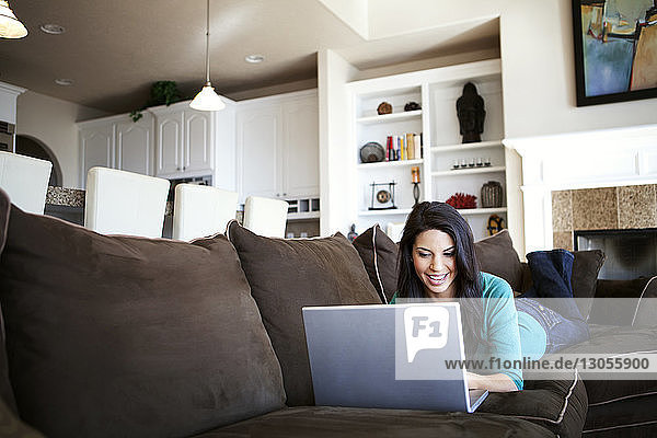Young woman using laptop while lying on sofa at home