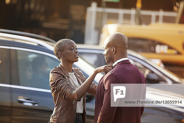 Woman adjusting collar of man while standing against car on road