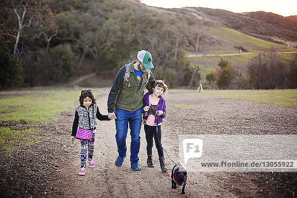 Father and daughters walking with dog on footpath against mountain