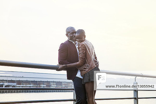 Cheerful couple standing by railing at pier against clear sky