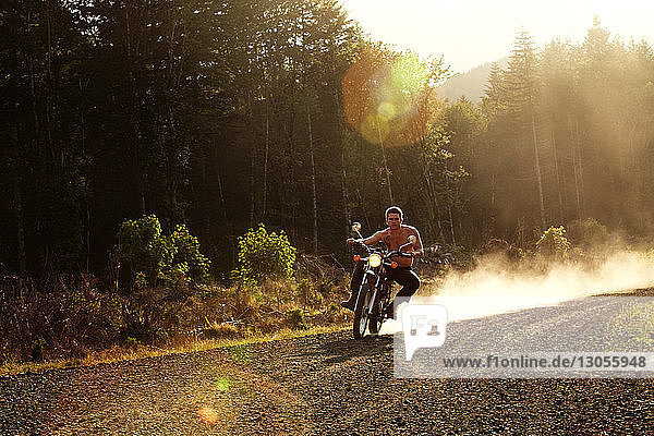 Man riding motorcycle on gravel road