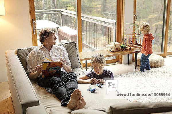 Father holding book while sons playing at home