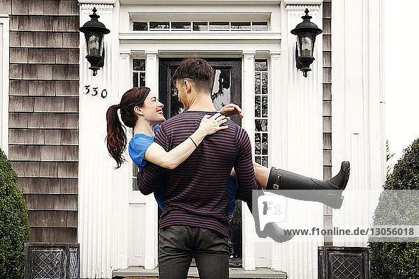 Mann trägt Frau  während er im Hinterhof steht