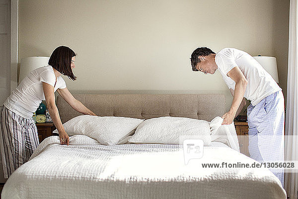 Couple arranging bed at home