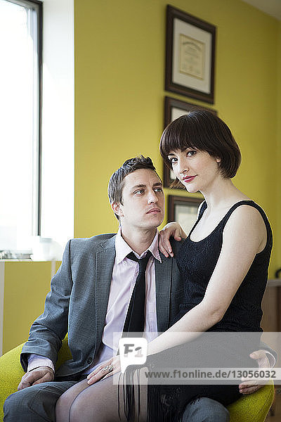 Man looking at girlfriend while sitting on armchair at home