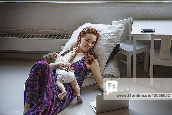 Mother with baby girl using laptop while lying on floor at home