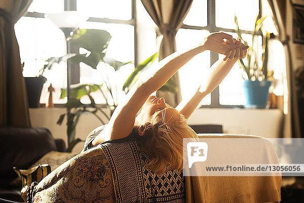 Frau streckt sich beim Anlehnen auf Sofa