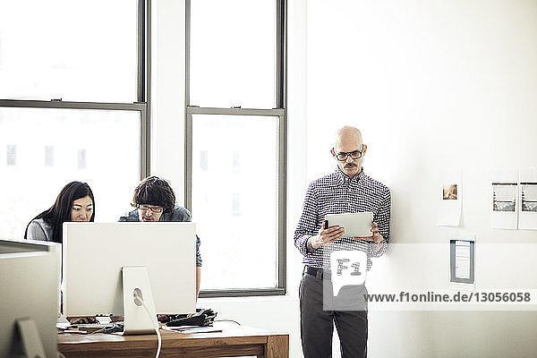 Geschäftsmann benutzt Tablet  während seine Kollegen im Büro am Computer arbeiten