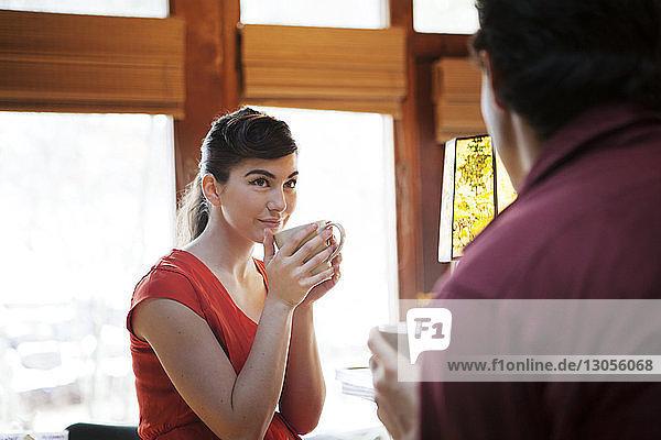 Frau trinkt Kaffee und sieht Mann im Café an