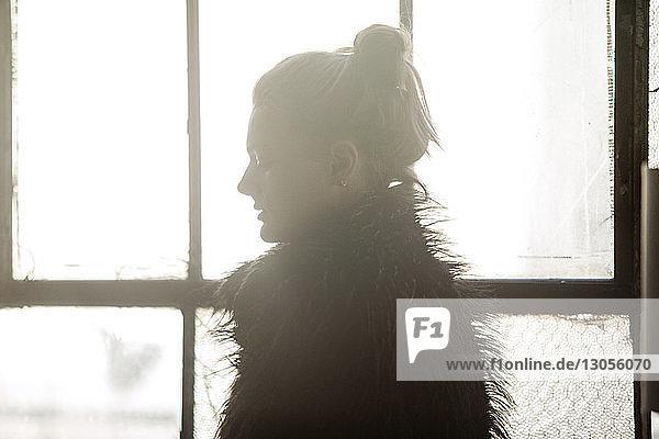 Frau im schwarzen Pelzmantel steht zu Hause am Fenster