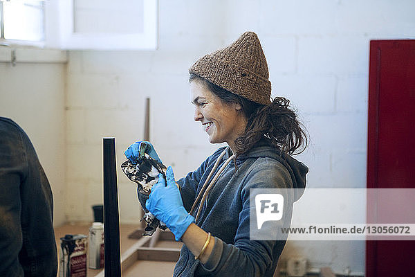 Side view of happy female carpenter in workshop
