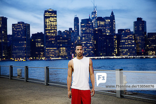 Portrait of sportsman standing on promenade by East River in city at dusk