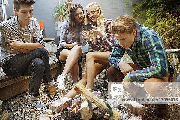 Frauen betrachten ein Foto  während sie bei Freunden am Lagerfeuer sitzen