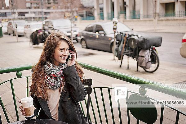 Glückliche Frau telefoniert  während sie im Straßencafé sitzt