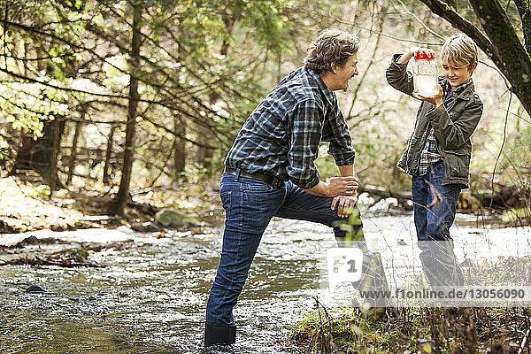 Vater und Sohn schauen Skorpione im Glas an  während sie am Fluss stehen