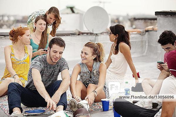 Glückliche Freunde genießen es  am Wochenende auf der Gebäudeterrasse zu sitzen