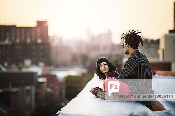 Frau sieht Mann an  der bei Sonnenuntergang auf Stützmauer sitzt