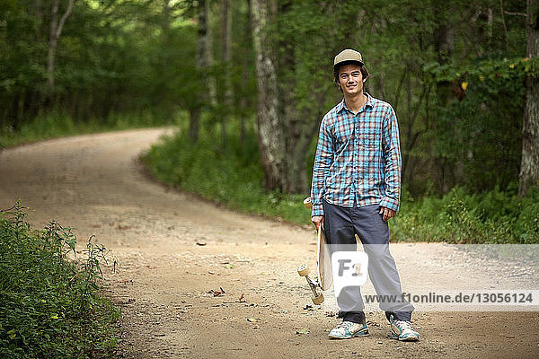 Portrait of man with skateboard standing on dirt road in forest