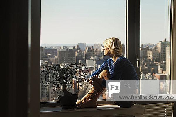 Seitenansicht einer Frau  die zu Hause am Fenster am Tisch sitzt