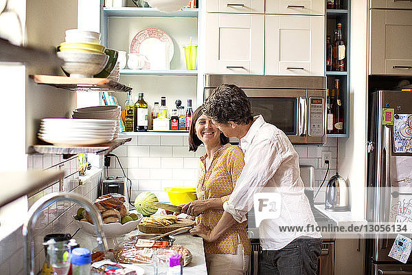 Loving couple standing at kitchen counter