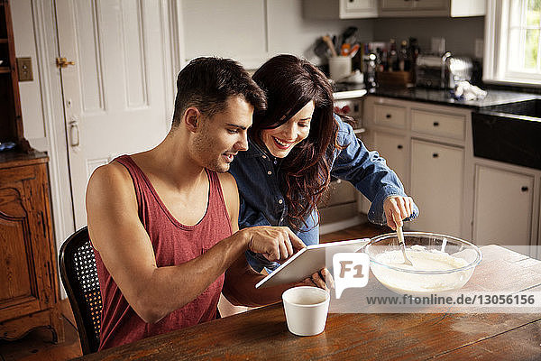 Man showing tablet computer to girlfriend in kitchen