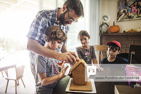 Family decorating gingerbread house at home