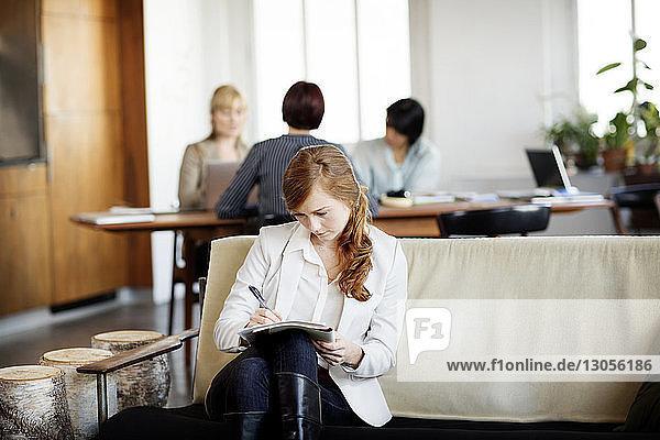 Geschäftsfrau schreibt in Buch mit Kollegen  die im Hintergrund arbeiten