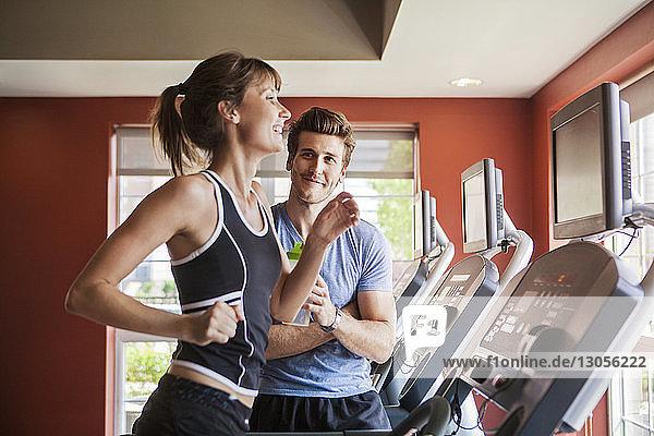 Mann schaut Frau an  die im Fitnessstudio auf dem Laufband läuft