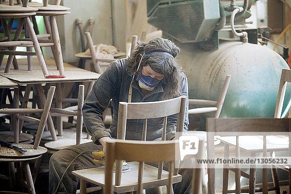 Female carpenter sanding wooden chair at workshop