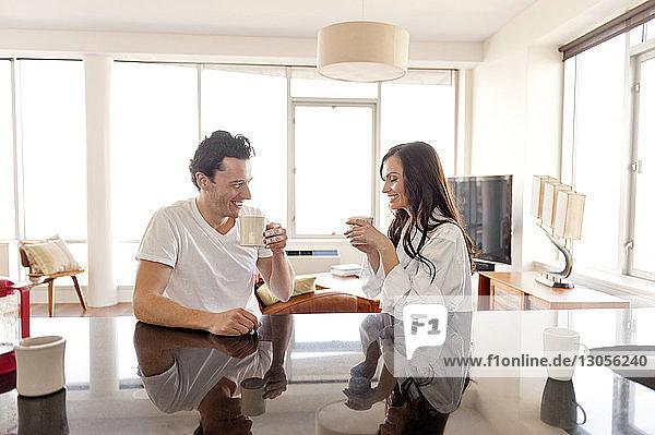 Fröhliches Paar trinkt zu Hause Kaffee auf dem Tisch