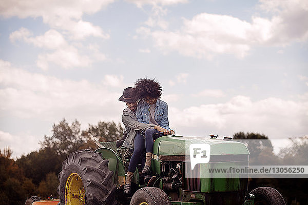 Woman sitting with man driving tractor against cloudy sky
