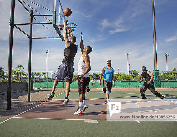 Men playing basketball in court on sunny day