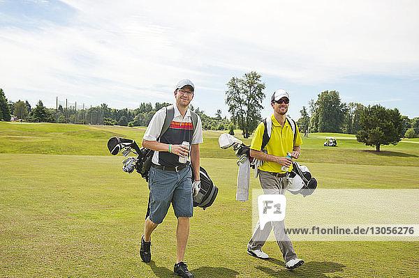 Male friends walking on golf course