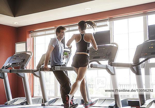 Glücklicher Mann schaut Frau an  die im Fitnessstudio auf dem Laufband läuft