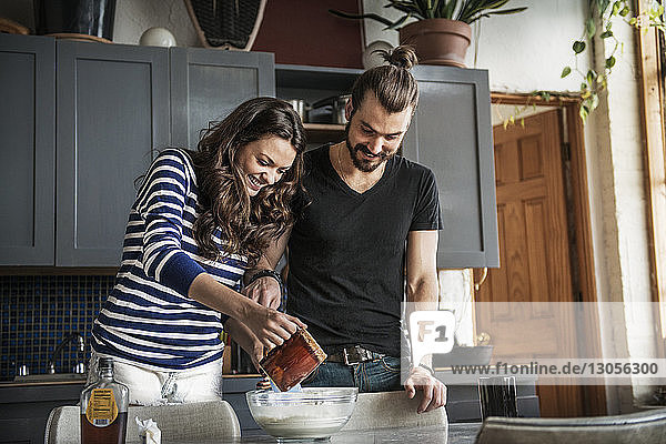 Happy young couple preparing food on table at home