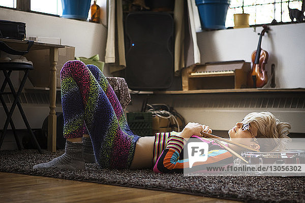 Woman lying on rug at home