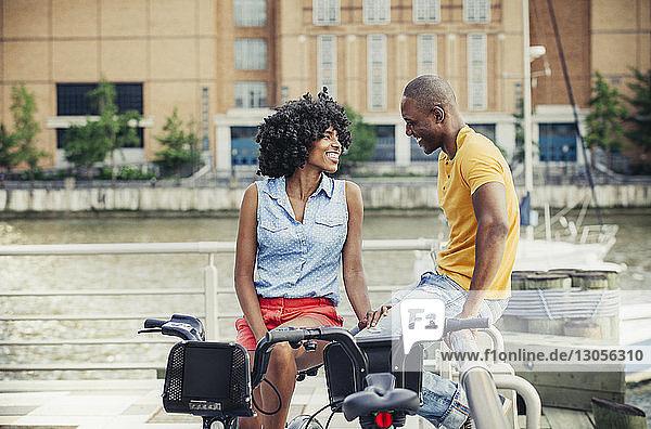Lächelndes Paar entspannt sich an Geländer an Promenade gegen Fluss