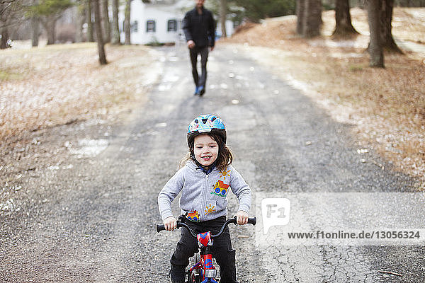 Boy riding bicycle on road with father in background