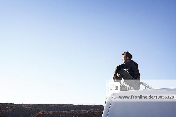 Seitenansicht eines nachdenklichen Mannes  der auf einem Wohnmobil sitzt