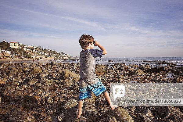 Junge schaut am Strand durch ein Fernglas