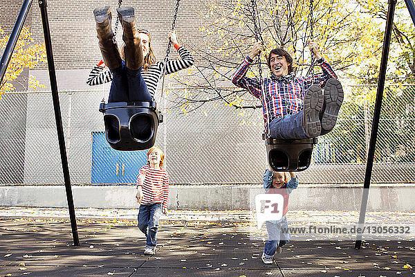 Kinder schubsen Eltern auf der Schaukel im Park