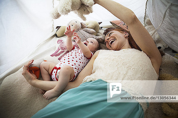 Cheerful mother playing with daughter in tent at home