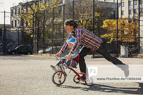 Vater schiebt Sohn auf Dreirad im Park