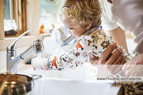 Cropped image of father holding son while washing hands at kitchen sink