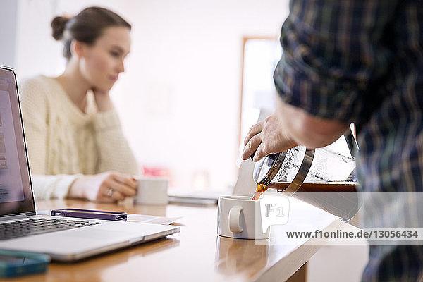 Mann gießt Kaffee in Tasse  während die Frau im Hintergrund arbeitet