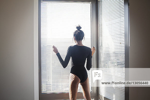Rear view of woman standing by blinds at home