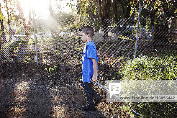 Side view of boy pulling push cart on street