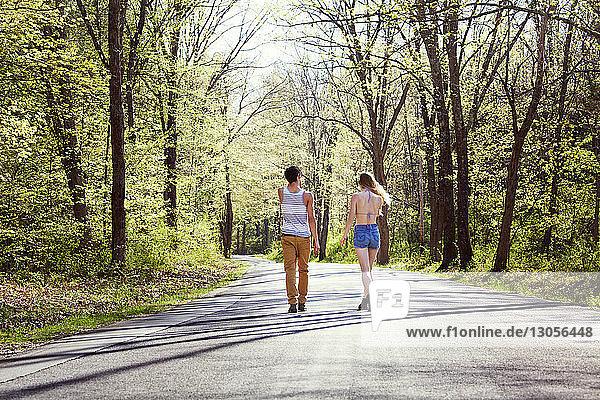 Rückansicht eines Paares  das auf einer Straße inmitten von Bäumen geht