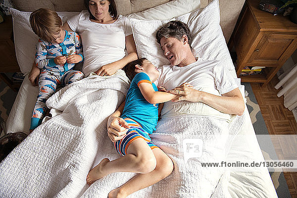 Overhead view of parents lying with children on bed at home